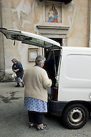 Switzerland. Canton Ticino. Corippo. Clarina Scettrini (right) buys in the early morning bread from the van which is a mobile bakery. Gabriela Scettrini (center), stands outside the church. Corippo lies in the Verzasca valley. With a population of just 16, Corippo is the smallest municipality in Switzerland. Despite this, it possesses the trappings of communities many times its size such as its own coat of arms, a town council consisting of three local citizens and a village church. A town council is a democratically elected form of government for small municipalities. A council may serve as both the representative and executive branch. The village has maintained its status as an independent entity since its incorporation in 1822. 8.05.13 © 2013 Didier Ruef