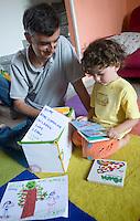 homeschooling, educazione parentale, educazione domestica.Il papà Matteo durante una lettura in inglese con Nichlas di tre anni.
