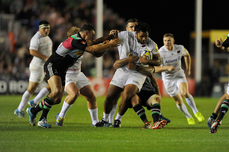 Billy Vunipola of Saracens is held by Joe Marler and Nick Easter of Harlequins during the Premiership Rugby Round 2 match between Harlequins and Saracens at The Twickenham Stoop on Friday 12th September 2014 (Photo by Rob Munro)