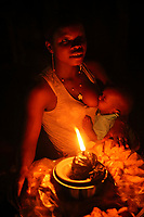 A woman breastfeeds a baby while running her food stall, which is lit by an oil lamp.