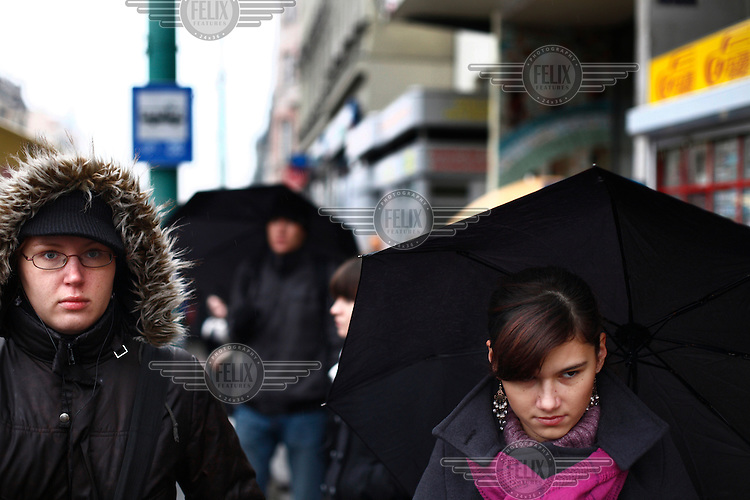 People in walking under umbrellas during a shower.