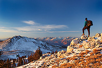 Male hiker in White Mountians at sunrise (Sierra Mountains in background), Inyo National Forest, White Mountains, California, USA