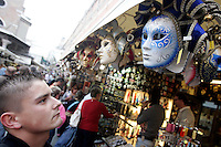 Maschere di Carnevale in vendita al mercato di souvenir al Ponte di Rialto, Venezia.<br /> A tourist looks at a carnival mask at the souvenir market of Rialto Bridge in Venice.<br /> UPDATE IMAGES PRESS/Riccardo De Luca