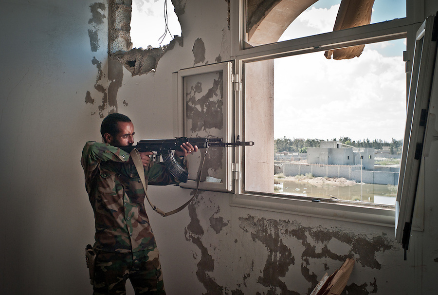 Anti-Gaddafi fighter fires his kalashnikov at a Gaddafi loyalist position in Sirte, Libya.