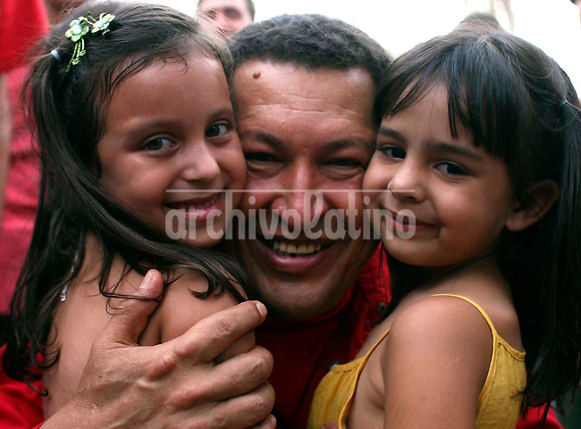 Venezuelan President Hugo Chavez poses for a picture with two small girls during a visit to Barinas country side.