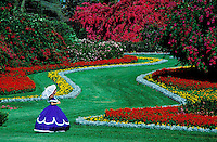 USA, Florida, Cypress Gardens. Woamen in period dress and parasol strolling through colorful gardens with bougainvillea in bloom..
