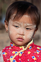 Myanmar, Burma.  Little Burmese Girl of Pre-School Age, Intha Ethnic Group, Inle Lake, Shan State.  She has thanaka paste on her face, a cosmetic sunscreen.