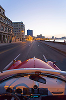 Vintage cars driving along Malecon road - viewed from one of the cars at dawn, Havana, Cuba