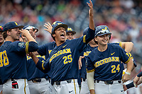 Michigan Wolverines pitcher Isaiah Paige (25) laughs with teammates Jack Weisenburger (48) and Casey Buckley (24) before their game against the Florida State Seminoles during the NCAA College World Series on June 17, 2019 at TD Ameritrade Park in Omaha, Nebraska. Michigan defeated Florida State 2-0. (Andrew Woolley/Four Seam Images)