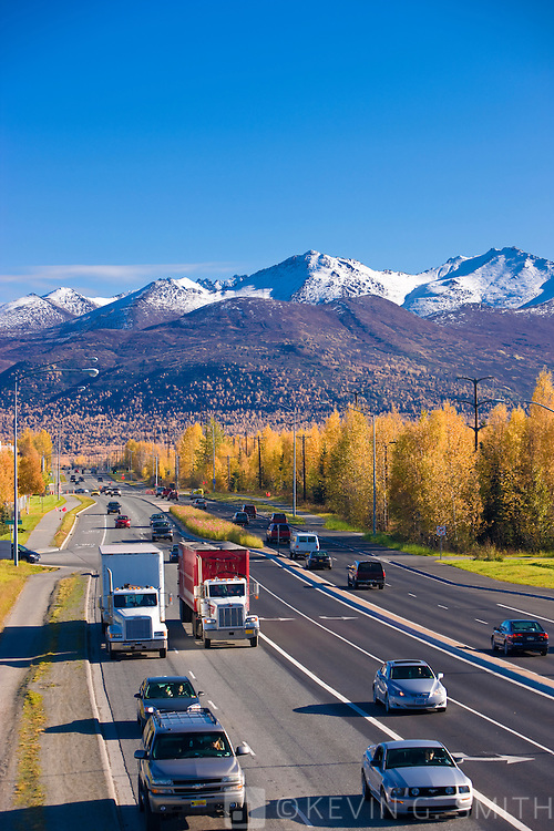 Traffic on  Muldoon road looking east towards the Chugach Mountains, Anchorage, fall, Anchorage, Southcentral Alaska, USA.