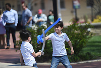 Eli Henry, 5, of Bentonville (from left) and Max Henry, 6, play fight with balloon swords, Sunday, April 4, 2021 at the downtown square in Bentonville. Check out nwaonline.com/210405Daily/ for today's photo gallery. <br /> (NWA Democrat-Gazette/Charlie Kaijo)