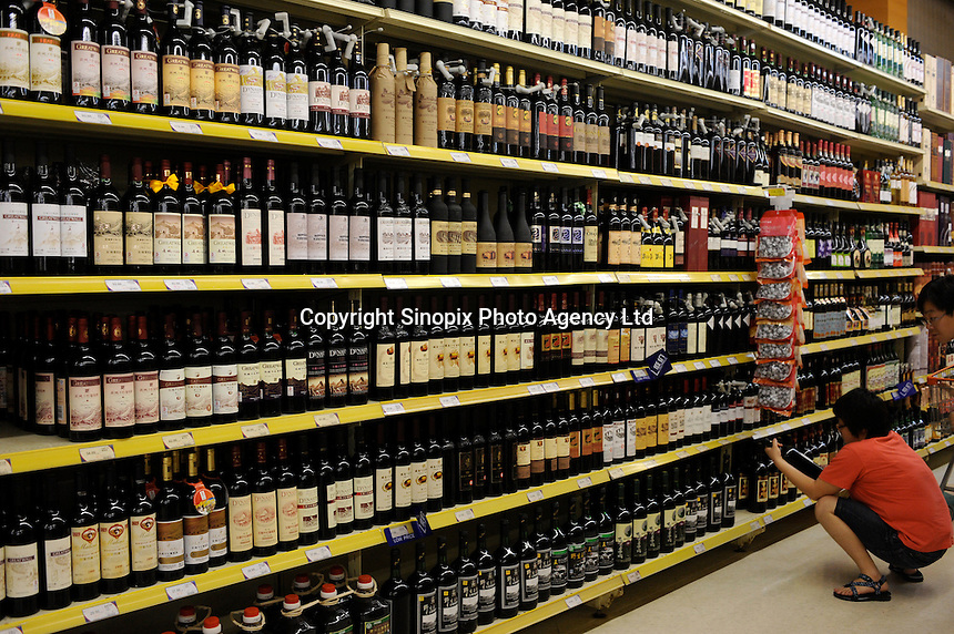 Locals shop for wine on a sunday afternoon in Shenyang, China. The British retailer is undergoing an aggressive expansion and attempting to capture the growing middle class market in food and other domestic merchandise in China..