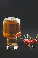 Glass of Beer, Froth, and Foam next to Bunch of Radishes, Still Life, Black Background