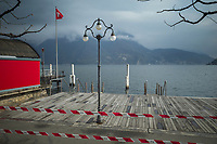 """Switzerland. Canton Ticino. Lugano. A police line forbids the access to the lake because of coronavirus (also called Covid-19). Due to the spread of the coronavirus , the Federal Council has categorised the situation in the country as """"extraordinary"""". It has issued a recommendation to all citizens to stay at home, especially the sick and the elderly. The Federal Council (German: Bundesrat, French: Conseil fédéral, Italian: Consiglio federale, Romansh: Cussegl federal) is the seven-member executive council that constitutes the federal government of the Swiss Confederation. From March 16 the government ramped up its response to the widening pandemic, ordering the closure of bars, restaurants, sports facilities and cultural spaces. Only businesses providing essential goods to the population – such as grocery stores, bakeries and pharmacies – are to remain open. Lake Lugano (also called Ceresio) is a glacial lake which is situated on the border between southern Switzerland and Northern Italy. The flag of Switzerland displays a white cross in the centre of a square red field. The white cross is known as the Swiss cross. 22.03.2020 © 2020 Didier Ruef"""