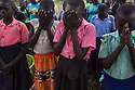 Uganda - Palorinya Refugee Camp - South Sudanese refugees pray before lessons start at school. <br /> Lack of structures, schooling material and qualified teachers within the refugee camps is having a devastating effect on the education of South Sudanese minors. The dropout rate is very high and local elders are afraid this might be connected to a recent spike in HIV rate, crime, drug consumption and underage pregnancies among youth