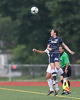Seacoast United Phantoms player Kylie Murphy (4) battles for head ball.  In a Women's Premier Soccer League (WPSL) match, Boston Aztec (white) defeated Seacoast United Phantoms (blue), 3-0, at North Reading High School Stadium on Arthur J. Kenney Athletic Field on on June 25, 2013.