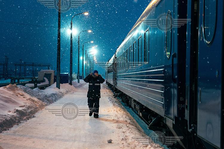 A member of the train staff walks alongside an Obskaya-Bovanenkovo railway train that is about to depart taking workers to the Gasprom Bovanenkovo gas field.