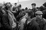 Teenagers at the Badminton Horse trials Gloucestershire 1985. Boys drinking cider from a bottle and with bear mascot fixed to his  brown fedora hat 1980s. UK