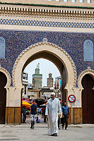 Fes, Morocco.  Man in Traditional Djellaba Leaving Fes El-Bali (Old City) through the Bab Boujeloud.  The minaret of the Bou Inania medersa is in the background.