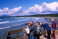 Senior Tourists photographing and whale watching at Wickaninnish Beach, Pacific Rim National Park Reserve, West Coast of Vancouver Island, BC, British Columbia, Canada