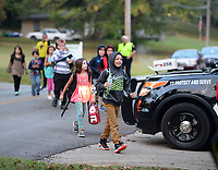 Greenland students cross Wilson Street Wednesday, Oct. 6, 2021, with help from Greenland Police Chief Gary Ricker as they take part in the school district's observance of National Walk to School Day in Greenland. Started in 1997 by the Partnership for a Walkable America, National Walk to School day is held on the first Wednesday in October in an effort to raise awareness of the healthy and environmental benefits to walking or biking to school. Visit nwaonline.com/211007Daily/ for today's photo gallery.<br /> (NWA Democrat-Gazette/Andy Shupe)