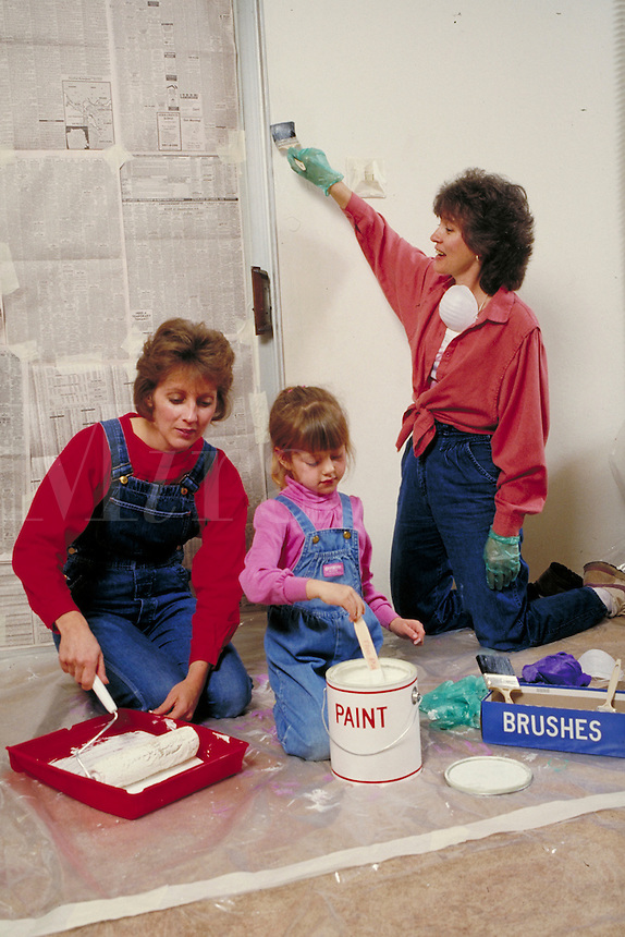 EXTENDED CAUCASIAN FAMILY MEMBERS PAINTING A WALL. THREE FEMALES, TWO ADULTS , ONE CHILD. OAKLAND CALIFORNIA USA.