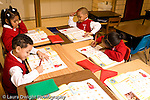 K-8 Parochial School Bronx New York Kindergarten students writing in math workbooks horizontal