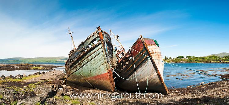 Derelict fishing boats abandoned on shoreline. Isle of Mull, Inner Hebrides, Scotland, UK. June 2010.