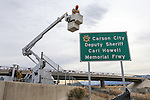 NDOT workers unveil a freeway sign dedicating I-580 in honor of Carson City Sheriff's Deputy Carl Howell in Carson City, Nev., on Tuesday, Dec. 8, 2015. Dep. Howell was killed in the line of duty Aug. 15, 2015. <br /> Photo by Cathleen Allison/Nevada Photo Source