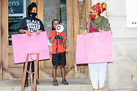 """Rally organizer Naheem Benalfew, 7, (center) speaks to the crowd as sister and co-organizer Anaysha Benalfew, 10, and community organizer Mela Miles, look on at the start of the """"Peaceful Children's March: Be the Change"""" demonstration in support of Black Lives Matter in Boston, Massachusetts, on Sun., June 7, 2020. The children's march was organized by siblings Naheem, 7, and Anaysha Benalfew, 10. The demonstration is part of a weeks-long nationwide response to the killing of George Floyd by Minneapolis police on May 25, 2020. The march started near the Nubian Square bus depot and continued to the nearby Boston Police Department headquarters, where marchers knelt for 8 minutes and 46 seconds, the time that police officers knelt on George Floyd's neck during his killing. A number of children, mostly people of color, then spoke about how people should be treated equally and how they wished they didn't have to grow up fearful that a police officer would kill them or their loved ones.  The signs here read """"Black Lives Matter"""" and """"just for Floyd."""""""