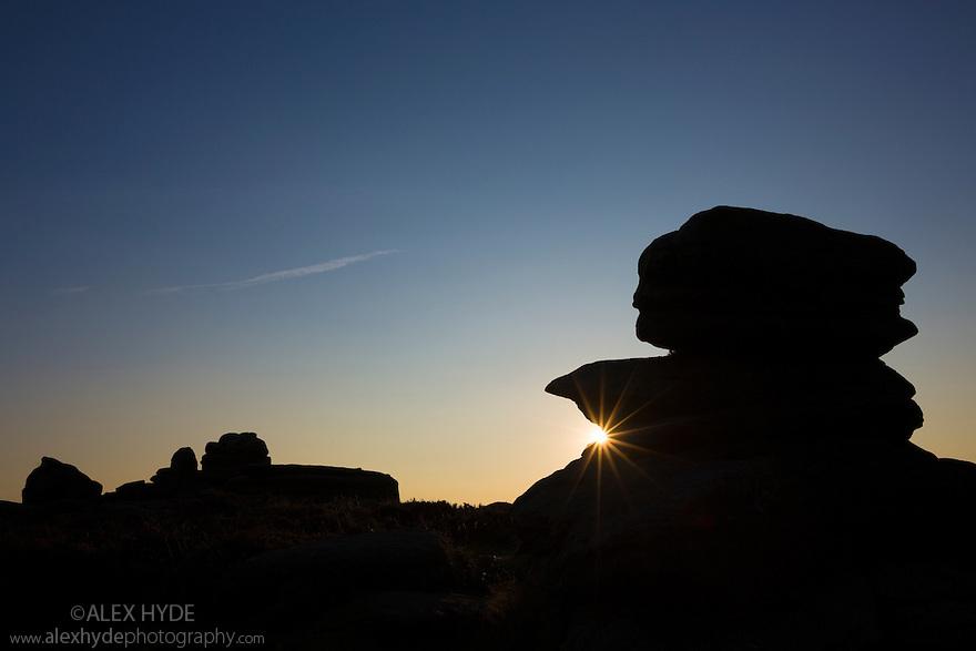 Over Owler Tor silhouetted at sunset, Peak District National Park, Derbyshire, UK. September.