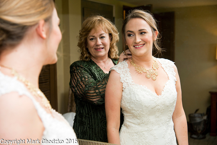 Mother puts the finishing touches on her daughter, the bride.