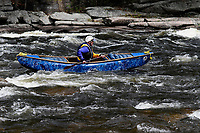Man paddling a canoe in the Hudson White Water Derby In North Creek in the Adirondack Mountains of New York State