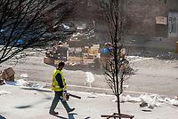 Milano, quartiere Bovisa, periferia nord. Operatore ecologico spazza rifiuti di plastica dopo il mercato --- Milan, Bovisa district, north periphery. Street cleaner sweeping plastic waste after the market