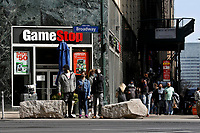 NEW YORK - NEW YORK - MARCH 23: People wait to cross the street in front of GameStop at 6th Avenue on March 23, 2021 in New York. GameStop stocks falls more than 10% after the video game store showing  strong earnings but lower than expected. (Photo by John Smith/VIEWpress)