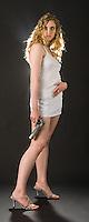 Caucasian blonde woman posing towards camera holding handgun on black seamless<br />
