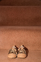 A pair of child's shoes on carpeted stairs