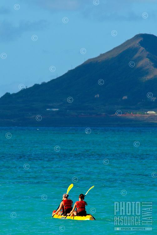 Two young women in a bright yellow kayak paddling through turquoise blue ocean, Kailua bay, Windward Oahu