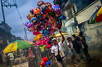 An Afro-Colombian balloon vendor walks in the street during the San Pacho festival in Quibdó, Colombia, 3 October 2019. Every year at the turn of September and October, the capital of the Pacific region of Chocó holds the celebrations in honor of Saint Francis of Assisi (locally named as San Pacho), recognized as Intangible Cultural Heritage by UNESCO. Each day carnival groups, wearing bright colorful costumes and representing each neighborhood, dance throughout the city, supported by brass bands playing live music. The festival culminates in a traditional boat ride on the Atrato River, followed by massive religious processions, which accent the pillars of Afro-Colombian's identity – the Catholic devotion grown from African roots.