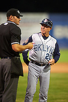 Brooklyn Cyclones manager Tom Gamboa (20) talks with umpire Dane Ponczak during a game against the Batavia Muckdogs on July 4, 2016 at Dwyer Stadium in Batavia, New York.  Brooklyn defeated Batavia 5-1.  (Mike Janes/Four Seam Images)