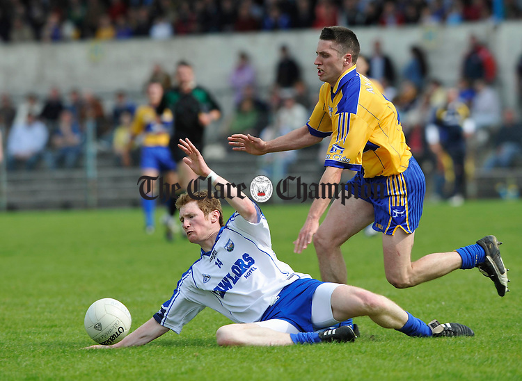 Liam O Lionain of Waterford goes down under pressure from Clare's  Gordon Kelly during their senior championship game in Cusack Park. Photograph by John Kelly.