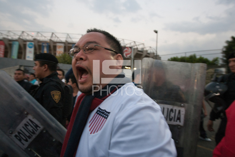 USA fan Brent Gamit and other fans walk into Azteca stadium escorted by Mexican police officers in riot gear that formed a perimeter between the USA and Mexican fans for the USA vs. Mexico World Cup Qualifier in Mexico City, Mexico on March 26, 2013.