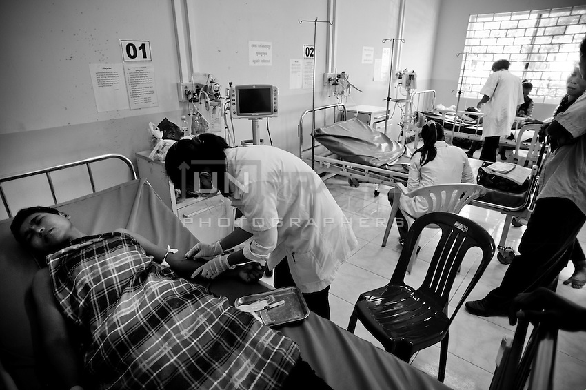 A young nurse carefully performing procedures with sutures and rising the wound. National Pediatric Hospital of Phnom Penh. Cambodia