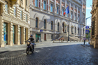 Fine Art Landscape Print Photograph. The dramatic lighting of this photograph emphasizes the action of the rider, the precision of his Motorbike, and the clean architectural lines of the buildings as the rider cruises down the street of Rome.