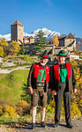Italien, Suedtirol, bei Meran, Dorf Tirol: 2 Suedtiroler in Lndestracht vor dem Landesmuseum Schloss Tirol, im Hintergrund die schneebedeckten Gipfel der Sarntaler Alpen | Italy, South Tyrol, Alto Adige, near Merano, Tirolo: 2 South Tyroleans in traditional dress standing in front of Tirol castle - provincial museum of history and culture, at background snowcapped summits of Sarntal Alps (Alpi Sarentine)