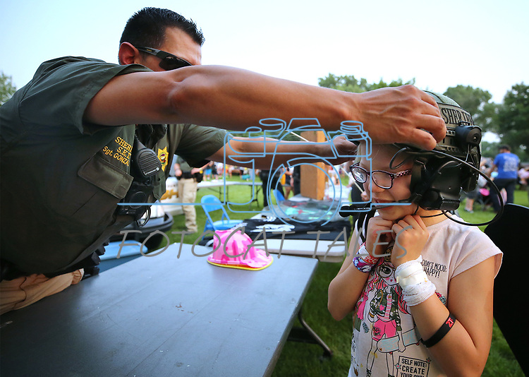 Carson City Sheriff's Sgt. Daniel Gonzales helps Lyric Adams, 7, try on a SET helmet during the 16th annual National Night Out event, hosted by the Carson City Sheriff's Office, in Carson City, Nev., on Tuesday, Aug. 7, 2018.<br />Photo by Cathleen Allison/Nevada Momentum