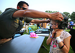 Carson City Sheriff's Sgt. Daniel Gonzales helps Lyric Adams, 7, try on a SET helmet during the 16th annual National Night Out event, hosted by the Carson City Sheriff's Office, in Carson City, Nev., on Tuesday, Aug. 7, 2018.<br />
