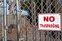 """A 'NO TRESPASSING"""" sign on a chainlink gate with a padlock."""
