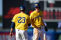 Michigan Wolverines Jimmy Kerr (15) shakes hands with assistant head coach Nick Schnabel (23) during a game against Army West Point on February 17, 2018 at Tradition Field in St. Lucie, Florida.  Army defeated Michigan 4-3.  (Mike Janes/Four Seam Images)