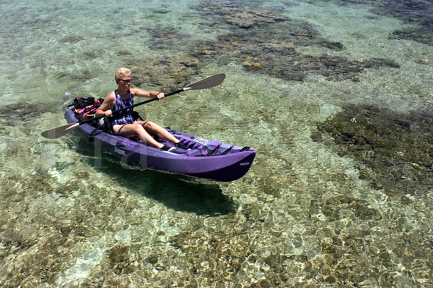 Woman (MR) with scuba diving equipment paddling a kayak over a shallow reef in Cayman Brac, Cayman Islands
